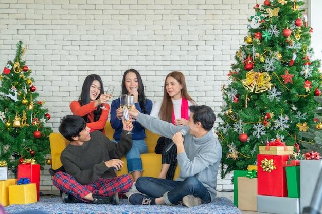 Weihnachtsfeier zeit. junge asiatische leute, die mit champagnerflöten rösten. freunde, die mit neuem jahr sich beglückwünschen.