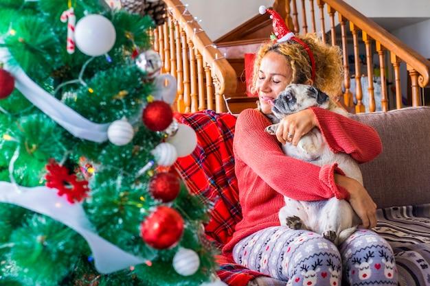 Weihnachtsfeiertag zu hause mit einer glücklichen kaukasischen jungen frau und einem lustigen süßen, entzückenden mopshund, der sich umarmt und zusammen spaß hat
