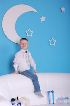 Weihnachtsfeiertage. kleiner junge auf einem weißen sofa mit weihnachtsgeschenkbox. blaue wand mit einem weißen mond an einer wand.