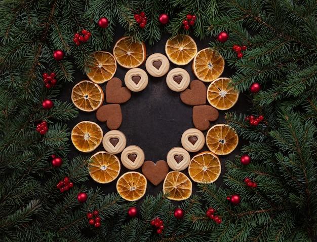 Weihnachtsfeiertags-kranzhintergrund mit herzformplätzchen, trockene orange scheiben, tannenbaum