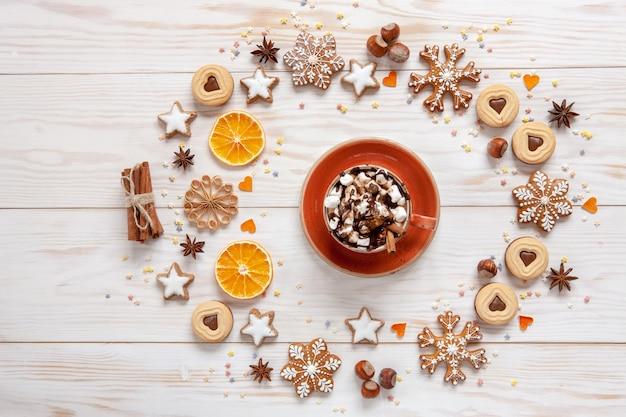 Weihnachtsfeiertags-kranzhintergrund mit selbst gemachten plätzchen, heißem getränk mit eibisch, trockenen orange scheiben, nüssen, gewürzen und kegeln