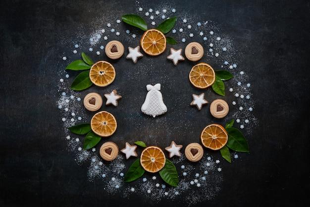 Weihnachtsfeiertags-kranzhintergrund mit selbst gemachten plätzchen, trockenen orange scheiben, grüne zitrusfrucht