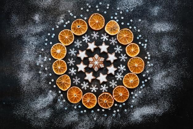 Weihnachtsfeiertags-kranzhintergrund mit selbst gemachten plätzchen, trockenen orange scheiben und pulverisiert