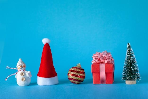 Weihnachtsfeiertagsfeierkonzept mit weihnachtsbaum und ball, weihnachtsmütze, geschenkbox, schneemann