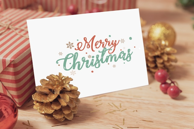 Weihnachtsfeiertagsgrußpapierkartendesignmodell mit dekoration auf hölzerner tabelle.