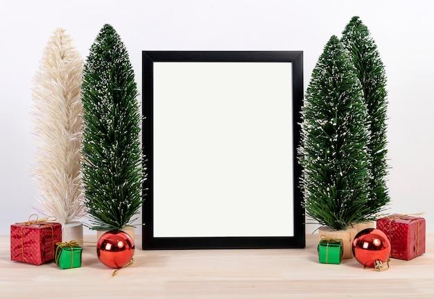 Weihnachtsfeiertagsgrußrahmendesignmodell mit dekoration auf hölzerner tabelle.