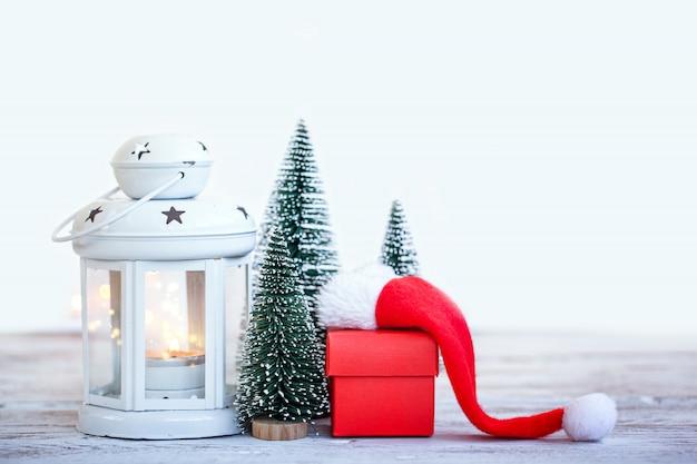 Weihnachtsfeiertagshintergrund mit dem baum mit drei tannen und rotem kasten. grußkarte