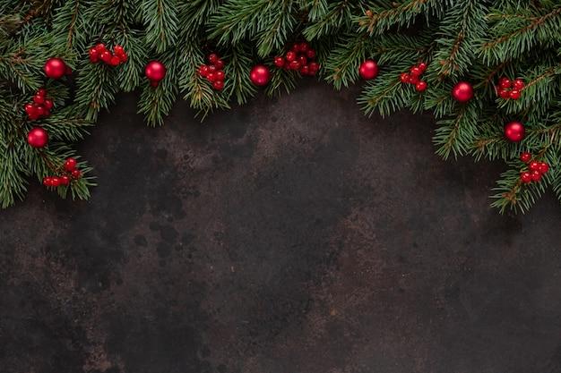 Weihnachtsfeiertagshintergrund mit tannenbaumniederlassungen mit roten beeren und bällen. draufsicht, abschluss herauf dunklen konkreten hintergrund.