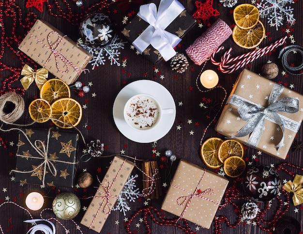 Weihnachtsfeiertagskaffeetasse-getränkgeschenkbox auf verzierter festlicher tabelle mit kiefernkegel-zuckerstangekerze