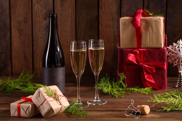Weihnachtsfeiertagstabelle mit gläsern und eine flasche und geschenke