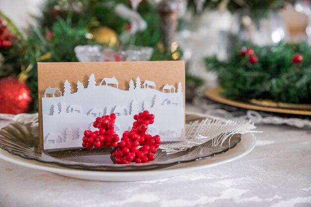 Weihnachtsfeiertagstabelle mit verzierungen, stechpalmenbeere, bogen und weihnachtsdekorationen in der weinleseart. weihnachten tischdekoration.