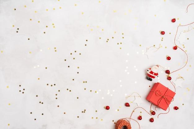 Weihnachtsfeiertagswinterdekoration mit roten geschenkboxen, seil, weinlesedekorationsstützen vorbei auf weißem hintergrund mit konfettis