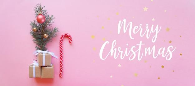 Weihnachtsfeiertagszusammensetzung auf rosa wand mit dem beschriften von frohen weihnachten