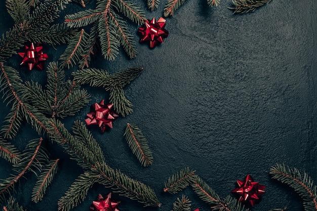 Weihnachtsfeiertagszusammensetzung mit tannenzweig und roten schleifen auf dunklem hintergrund. flache lage, draufsicht, kopierraum.