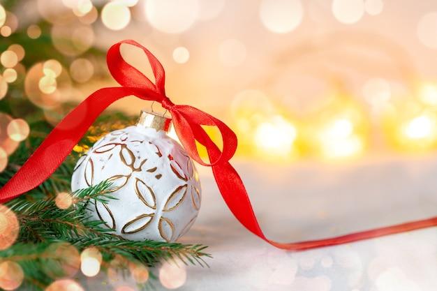 Weihnachtsfeiertagszusammensetzung mit weißem ball und rotem band auf hellem hintergrund mit kopienraum. frohe weihnachten und neujahr urlaub hintergrund.