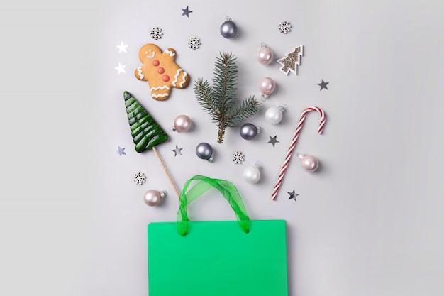 Weihnachtsferien einkaufen konzept. grüne tasche mit festlichen geschenken, zuckerstange, leckereien, dekor, glitzerkonfetti