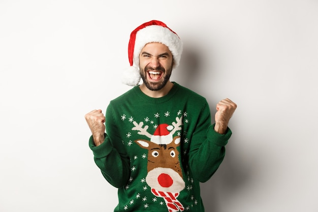 Weihnachtsferien, feiern und partykonzept. fröhlicher kerl in weihnachtsmütze und pullover, faustpumpen machen und sich freuen, triumphieren und auf weißem hintergrund stehen
