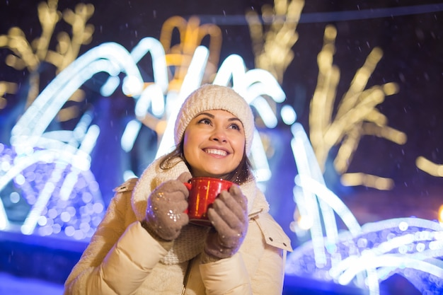 Weihnachtsferien schöne lächelnde frau in warmer kleidung mit tasse heißem kaffee im freien im winter
