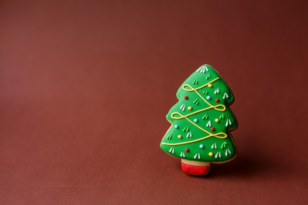 Weihnachtsferien süßigkeiten. weihnachtstraditionen. weihnachtsbaumlebkuchen am dunkelroten copyspace-feiertag