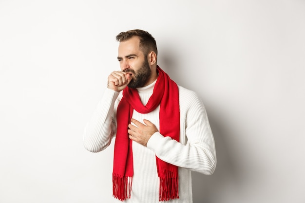 Weihnachtsferien und feierkonzept. mann fühlt sich krank, hustet und verzieht das gesicht von halsschmerzen, covid-19-symptome an silvester, stehend auf weißem hintergrund. Kostenlose Fotos