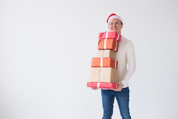 Weihnachtsferien und präsentiert konzeptmann in sankt-hut, der viele geschenke auf weißem hintergrund hält