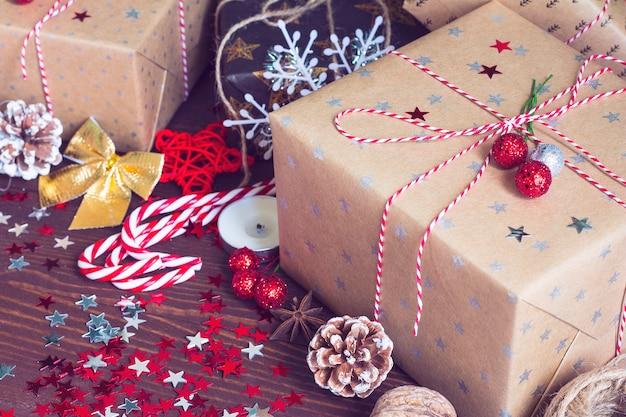 Weihnachtsferiengeschenkbox auf verzierter festlicher tabelle mit kiefernkegel-zuckerstangennüssen und schein spielt auf hölzernem hintergrund die hauptrolle