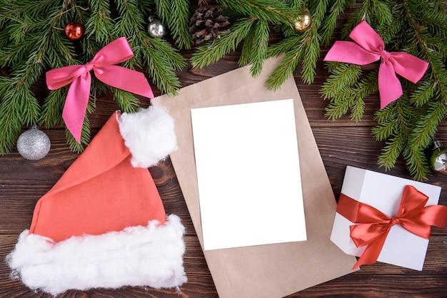 Weihnachtsferienhintergrund. geschenke mit einem roten band, weihnachtsmütze und dekor unter einem weihnachtsbaum auf einem holzbrett. nahansicht. kopieren sie platz an die tafel.