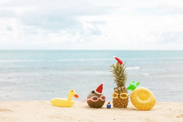 Weihnachtsferienkonzept am tropischen strand. früchte mit weihnachts- und sommeraccessoires