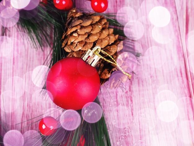 Weihnachtsferienkranz mit kugeln auf rustikalem rotweißem holz.