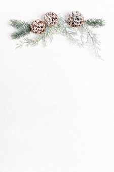 Weihnachtsfest festliche weihnachtsdekorationen aus ästen und tannenzapfen auf leerem weißem blatt mit schnee
