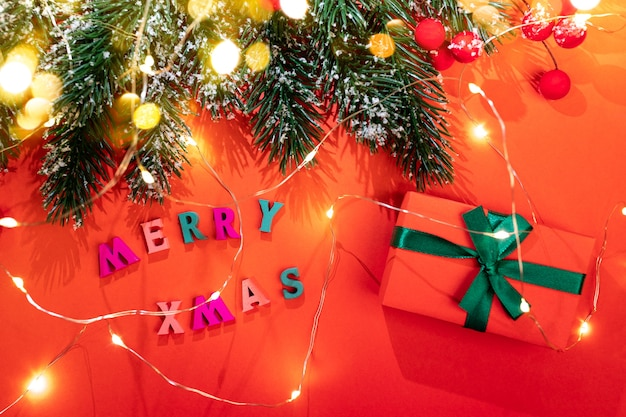 Weihnachtsfestgrußkarte. tannenzweige und leuchtende weihnachtslichter mit schönen schatten, schnee, roten beeren, farbbuchstaben frohe weihnachten, diy-geschenkbox, goldene bokeh-lichter auf rotem hintergrund. draufsicht.