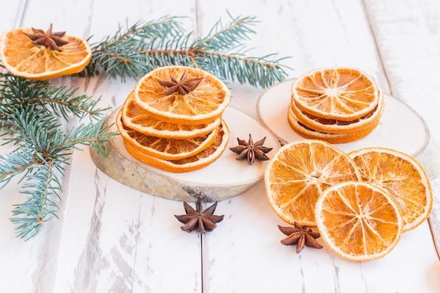 Weihnachtsfestivw-hintergrund mit tannenzweigen, getrockneten orangen und anissternen auf rustikalem holztisch