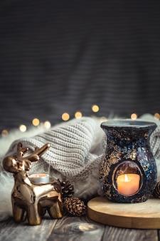 Weihnachtsfestkomposition mit spielzeughirsch, goldenen lichtern und kerzen auf hölzernem decktisch und winterpullover