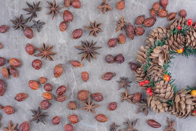 Weihnachtsfestkranz mit tannenzapfen und sternanis auf marmorhintergrund.