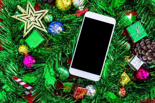 Weihnachtsfestliche dekorationen mit leerem smartphone auf rotem papierhintergrund, neues jahr conc