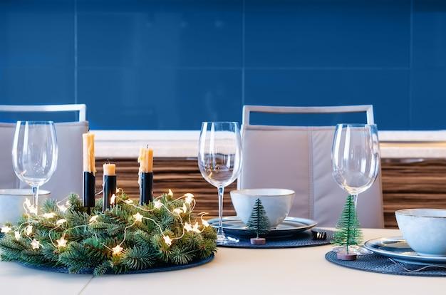Weihnachtsfestliche tischdekoration mit fichtenkranz. klassische blaue farbe im modernen interieur.