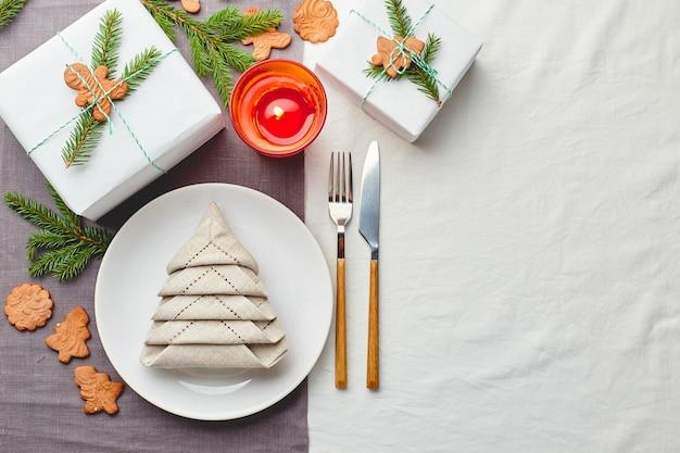Weihnachtsfestliche tischdekoration, serviette in form von weihnachtsbaum auf einem teller auf weißer tischdecke mit geschenken und dekorationen mit tannenzweigen und lebkuchen