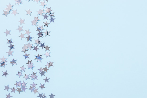 Weihnachtsfestlicher abstrakter hintergrund mit konfetti-sternen aus silberfolie auf blau