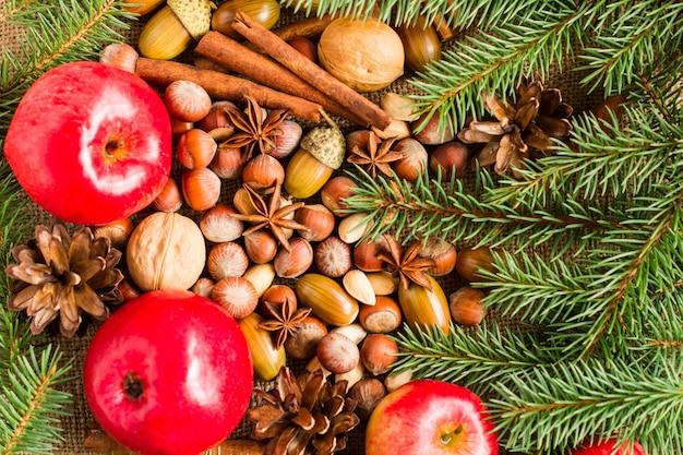 Weihnachtsfestlicher hintergrund mit fichtenzweigen, zapfen mit waldstillleben und natürlichen zutaten. ansicht von oben.