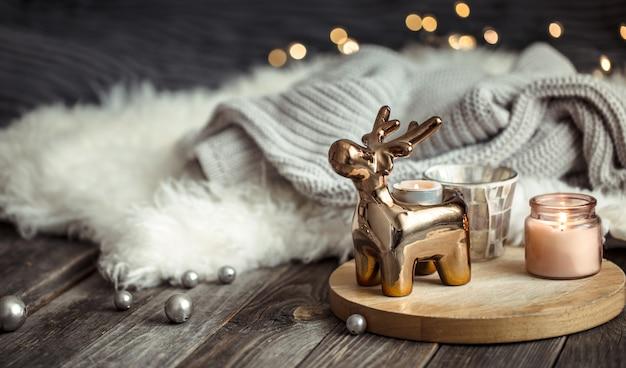 Weihnachtsfestlicher hintergrund mit spielzeughirsch, unscharfer hintergrund mit goldenen lichtern und kerzen, festlicher hintergrund auf hölzernem decktisch und winterpullover auf hintergrund