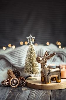 Weihnachtsfestlicher hintergrund mit spielzeughirsch, unscharfer hintergrund mit goldenen lichtern und kerzen