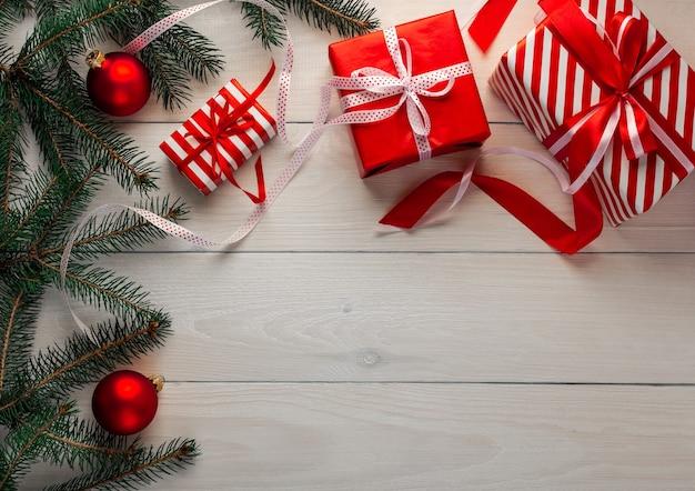 Weihnachtsfestlicher hintergrund, schöne geschenke mit bändern und schleifen, zweige der grünen fichte mit weihnachtsdekorationen auf einem weißen hölzernen hintergrund
