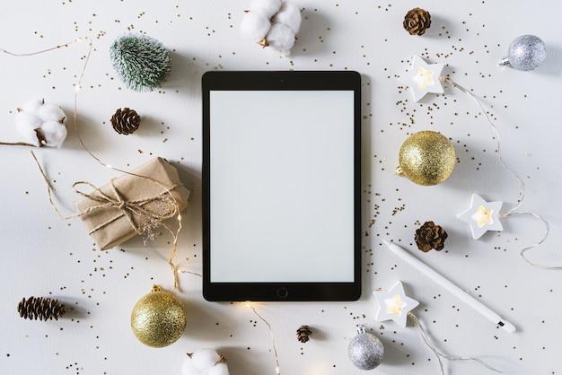 Weihnachtsfestschmuck und die tafel mit bleistift. mit wunschliste und zielkonzept. tablette, geschenk und coton zweig mit glänzenden goldenen kugeln. neujahr flach legen, draufsicht, kopierraum.