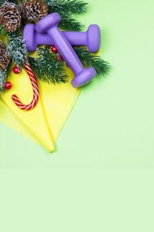 Weihnachtsfitness. gesundes und aktives lebensstilkonzept. lila hanteln, gelbes gummiband, süßigkeiten und tannenbaum auf grün