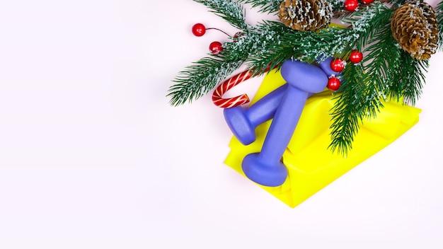 Weihnachtsfitness. gesundes und aktives lebensstilkonzept. lila hanteln, gelbes gummiband, süßigkeiten und tannenbaum auf rosa