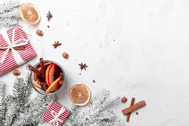 Weihnachtsflache draufsicht auf weißgrauer betonhintergrundtisch mit glühweinglastasse oder -becher, präsentieren rote geschenkboxen, dekorationen, zimt, orangenscheiben, gewürze, tanne. foto zur weihnachtszeit