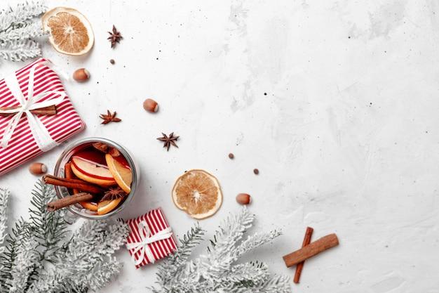 Weihnachtsflache draufsicht mit glastasse glühwein-geschenkbox-dekorationen