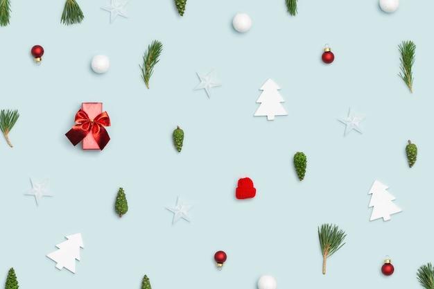 Weihnachtsflachlage mit winterdekor tannenzweigen grüner kegel rot spielzeug ball geschenkbox schneeball