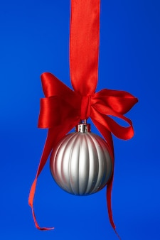 Weihnachtsflitter, der am roten satinband gegen blau hängt