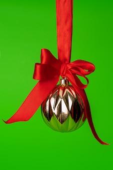 Weihnachtsflitter, der am roten satinband gegen grünen hintergrund hängt